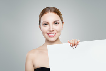 Perfect model girl showing white empty paper signboard for advertising marketing or product placement