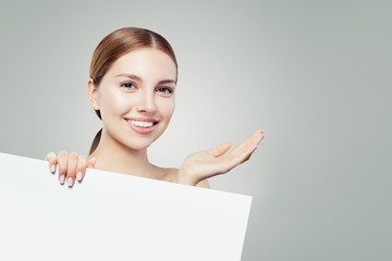 Young perfect girl laughing and showing empty open hand and white paper banner board background for advertising marketing or product placement
