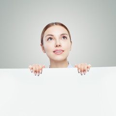 Happy woman looking up and holding white empty paper board background with copy space for advertising marketing or product placement
