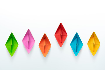 Multicolored paper boats on a white background, business competition concept with copy space