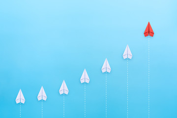 Leadership concept with red paper plane leading among white on blue background with copy space Wall mural