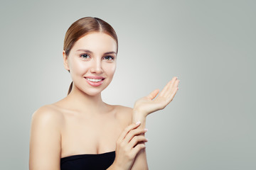 Cute gitl smiling and holding empty open hand. Facial treatment, face lifting, anti aging and skin care cosmetics concept.