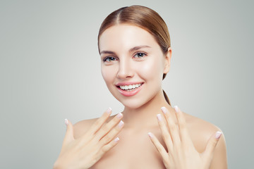 Excited woman with healthy clear skin, cute smile and french manicure hand. Cosmetology offer concept