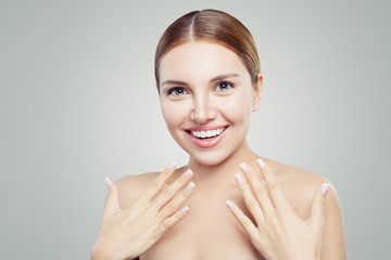 Surprised girl with healthy skin, cute smile and french manicure hand. Cosmetology offer concept