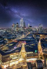 Fototapete - Blick über die Dächer der Skyline von London auf die City bei Nacht mit Sternenhimmel