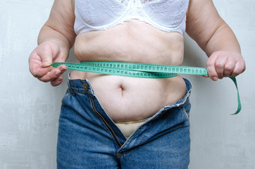 Woman with huge belly, get upset and tightening the measure tape on her waist.Concept of unhealthy eating