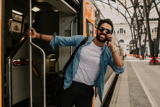 Confident Attractive young hispanic wearing sunglasses and blue shirt male holding smartphone hand and calling to friends while he standing at the train wagon on platform.