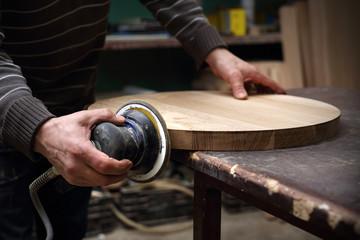 Fototapeta Szlifowanie desek. Stolarz szlifuje drewniany blat. obraz