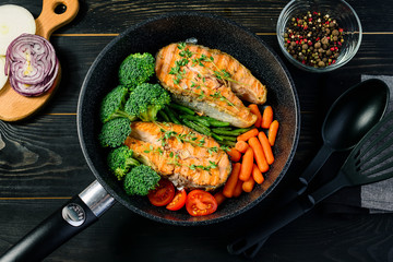 grilled salmon fillet with broccoli and vegetables in a pan