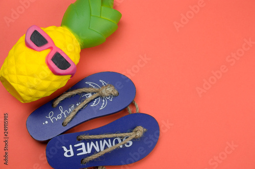 4a92778a288c top view decorative wooden flip flops and squishy toy pineapple on a coral  background copy space