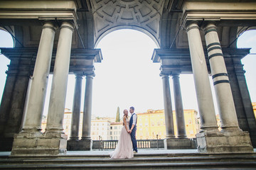 Young beautiful wedding couple is standing on the street in Florence. bride in beautiful dress. The groom is stylishly dressed