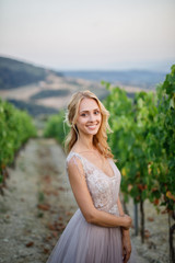 young beautiful wedding bride walks at sunset in Tuscany in Italy near the vineyards in a beautiful dress