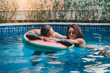 Mom and teenage daughter swimming together relax with watermelon rubber ring in pool at resort, Family vacation trip.