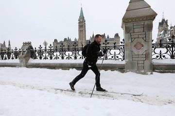 A man cross-country skis past Parliament Hill during a winter snow storm in Ottawa