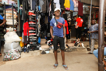 Charles Nwuzo, 19, poses for a picture outside a store in Abuja, Nigeria
