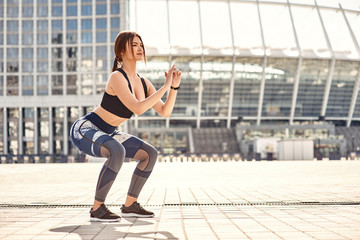Perfect squat. Sporty young woman in sport clothing doing squats while exercising outside in the morning