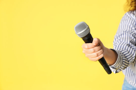 Young woman holding microphone in hand on color background. Space for text