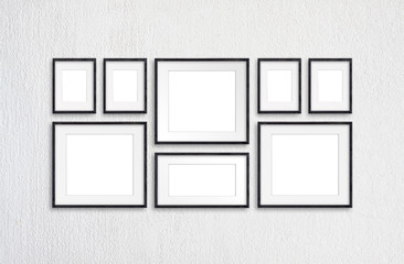 Black wooden realistic photo frames, eight frameworks collage on white plastered wall