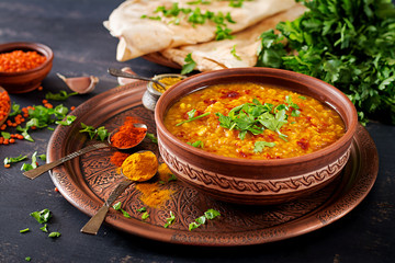 Indian dal. Traditional Indian soup lentils.  Indian Dhal spicy curry in bowl, spices, herbs, rustic black wooden background. Authentic Indian dish. Overhead Fotomurales