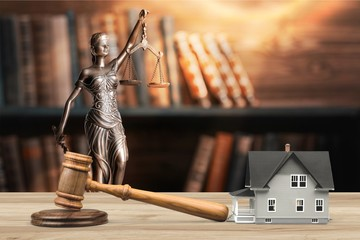 Wooden judge gavel and toy  house on  background
