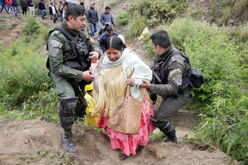 Police officers help a woman after a landslide due heavy rains in Mallasa district in La Paz