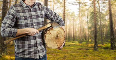A lumberjack with an ax in his hand and a log. Logger with checkered shirt. Plenty of copy space for your own text or product.