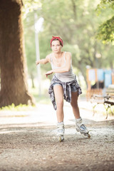 Young woman with inline skates in park having good time