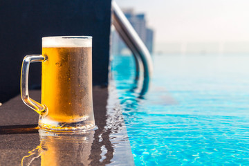 A glass of beer on a sunny day by the pool