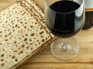 A glass of red wine, open wrapped baked matzo, on a wooden table.