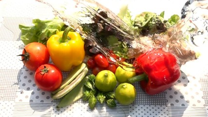 Fototapete - Pouring fresh water to the pile of mixed vegetables on the table in Slow Motion