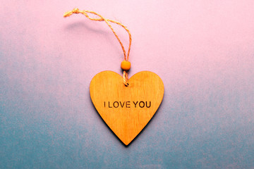 """A wooden heart with the words """"I love you"""", flat lay on gradient pink background, space for your records"""