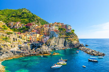 Fotobehang Liguria Manarola traditional typical Italian village in National park Cinque Terre, colorful multicolored buildings houses on rock cliff, fishing boats on water, blue sky background, La Spezia, Liguria, Italy