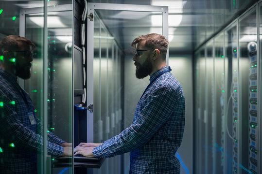 Bearded IT specialist setting servers in data center