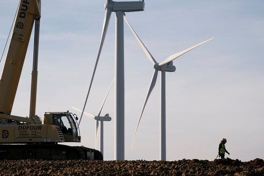 A worker walks past power-generating windmill turbines in a wind farm in Graincourt-Les-Havrincourt