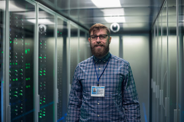 Adult bearded engineer in server room