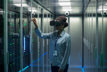 Technician works in a data center wearing a VR headset