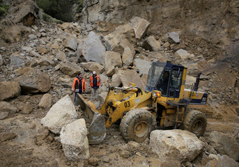 A bulldozer removes the debris after landslide due heavy rains in Mallasa district in La Paz