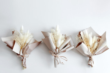 Dried flowers in minimalist bouquets on light background. Flowers composition. Flat lay, top view. Love, spring and gift concept.