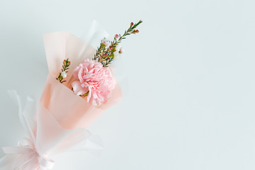 Spring flowers. Fresh bouquet with carnation in minimal style on light background. Top view, spring flat lay with copyspace for text. Love and gift concept