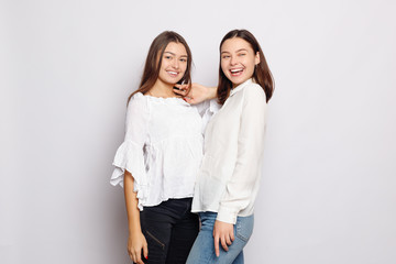 two laughing girls in white blank t-shirts looking into the camera