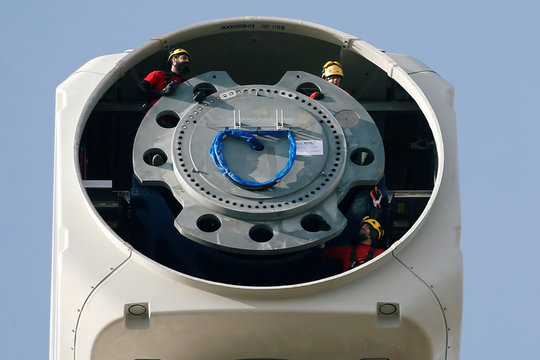 Workers are seen at the top of a power-generating windmill turbine as they attend to fix the propeller, in a wind farm in Graincourt-Les-Havrincourt