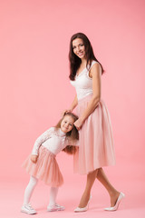pretty, charming mother and smiling daughter on pink background, hugging, looking at camera, women's day. Mother's day