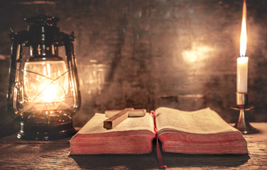 Holy bible with light of candle and oil lamp on wooden table. christian concept.