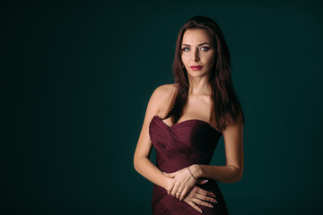 Portrait of magnificent sexy woman in evening dress posing over dark green background