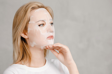 Beautiful woman in facial mask looking at camera, clean skin. Concept recovery, anti-aging