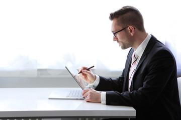 Geschäftsmann sitzt am Tisch mit Tablet und schreibt auf dem Display