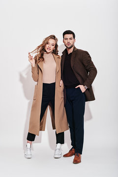 Looking perfect together. Attractive and well-dressed couple posing in studio. Isolated over grey background.
