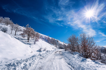 Mountain road covered by snow in backlight. Snow on the Nuoro's mountains in Sardinia, Bruncu Spina.