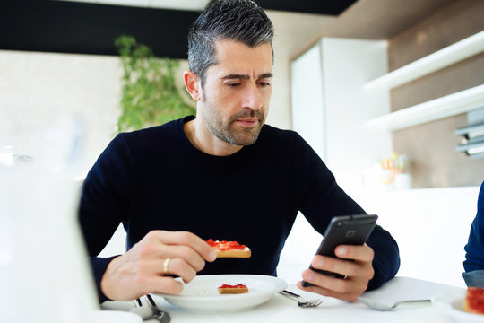 Handsome young man using his mobile phone while enjoying the breakfast with family in the kitchen at home.