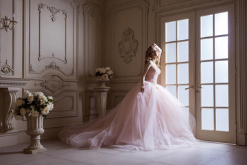 Beautiful young blond woman in luxurious long pink dress posing in vintage room interior. indoor studio shot.